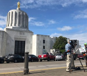 A TV reporter interviews self-employed logger Bridger Hasbrouck, of Dallas, Ore., outside the Oregon State House in Salem, Ore., on Thursday, June 20, 2019. (AP Photo/Gillian Flaccus)