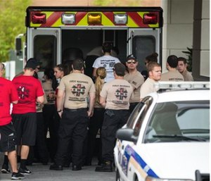 EMS first response personnel are seen outside a Hampton Inn & Suites hotel, which turned into a hub for families and friends waiting to hear about loved ones because of its proximity to the Orlando Regional Medical Center. (Loren Elliott/The Tampa Bay Times via AP)