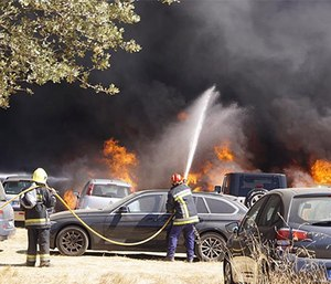 Firefighters respond to a parking lot blaze that destroyed over 400 cars. (Photo/Hugo Teixeira)