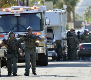 Riverside Country Sheriffs Deputies stand near the scene of a shooting in Palm Springs, Calif., Saturday, Oct. 8, 2016. (AP Photo/Rodrigo Peña)