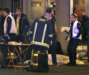 Rescue workers at the scene as victims lay on the pavement outside a Paris restaurant.  (AP Photo/Thibault Camus)