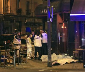 Medics attend the scene as victims lay on the pavement outside a Paris restaurant. Police report multiple terror incidents, including shootings, explosions and hostage taking, leaving many dead.