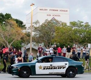 A police car drives near Marjory Stoneman Douglas High School in Parkland, Fla. (AP Photo/Terry Renna)