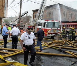 Philadelphia firefighters work to put out a fire at the American Legion Post 396, Monday. (Tom Gralish/The Philadelphia Inquirer via AP)