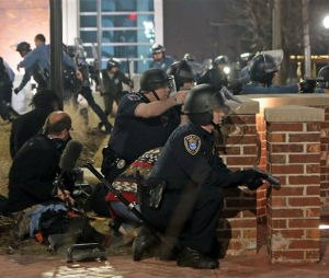 Police take cover after two officers were shot while standing guard in front of the Ferguson Police Station on Thursday, March 12, 2015.