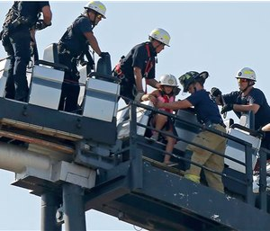 Oklahoma City firefighters rescue amusement park goers from a stalled roller coaster at Frontier City Wednesday. (Bryan Terry/The Oklahoman via AP)