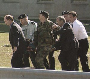 Secretary of Defense Donald Rumsfeld helps carry a patient to an ambulance after the attack at the Pentagon.