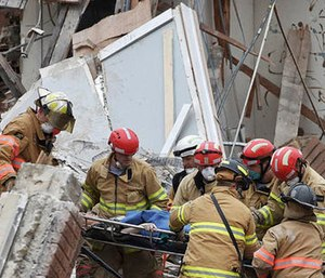 Emergency crews rescue a woman from a building collapse Friday Dec. 2, 2016 in downtown Sioux Falls. Two people were trapped inside the building, which was undergoing construction at the time of the collapse.
