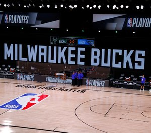 Referees huddle on an empty court at game time of a scheduled game between the Milwaukee Bucks and the Orlando Magic for Game Five of the Eastern Conference First Round during the 2020 NBA Playoffs on Aug. 26, 2020 in Lake Buena Vista, Florida. (Kevin C. Cox/Getty Images/TNS)