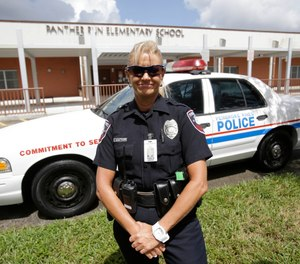 In this Thursday, Aug. 22, 2013 photo, Dara Van Antwerp, the school resource officer at Panther Run Elementary School is shown beside her patrol car at the school in Pembroke Pines, Fla. (AP Photo/Wilfredo Lee)