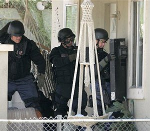 Phoenix SWAT team members prepare to move in on a house during a police standoff with an armed man in Phoenix on Friday, July 7, 2006. The man was wanted on a probation violation warrant. (AP Photo/Khampha Bouaphanh)