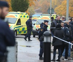 A crowd gathers outside, as emergency services attend the scene of a sword attack by a masked man at a school in Sweden. (Bjorn Larsson Rosvall / TT via AP)