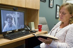 In this Sept. 10, 2014 photo released by the Nebraska Medical Center, Debbie Sacra reads Bible verses to her husband Dr. Richard Sacra via a video link in Omaha, Neb. Dr. Sacra is being treated for ebola at the biocontainment unit at the Nebraska Medical Center in Omaha, Neb. (AP Photo/Nebraska Medical Center, Max Sacra)