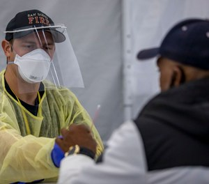 Firefighter Blake Heidrich helps Roderick Bradley self-administer his COVID-19 test at Operation Shelter to Home in the San Diego Convention Center. (Photo/David Poller)