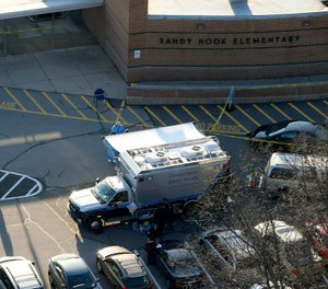 Officials stand outside of Sandy Hook Elementary School in Newtown, Conn., where gunman Adam Lanza opened fire inside school killing 20 first-graders and six educators at the school. (AP Photo/Julio Cortez, File)