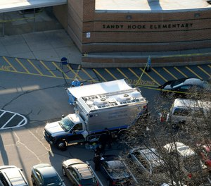 Officials stand outside of Sandy Hook Elementary School in Newtown, Conn., where gunman Adam Lanza opened fire inside school killing 20 first-graders and six educators at the school.