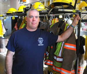 In this Nov. 4, 2016 photo, Scott Geiselhart stands next to turnout gear at the Frazee Fire Department fire hall in Frazee, Minn.