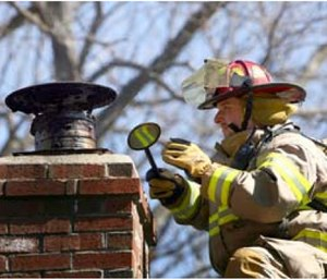 A Lancaster, Mass., firefighter operates at a chimney fire (Photo Scott LaPrade).