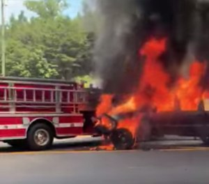 The video shows an on-fire pickup truck – that's also towing a camper trailer – roll downgrade toward the fire truck and ultimately come to rest against the fire apparatus. (Photo/Facebook)