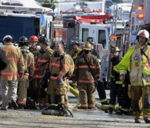 Firefighters stand by the scene of a fire after a wall collapsed in York, Pa. (John A. Pavoncello/York Dispatch via AP)