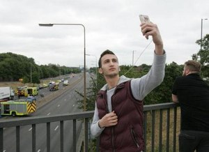 Man taking a selfie in front of a motor vehicle collision