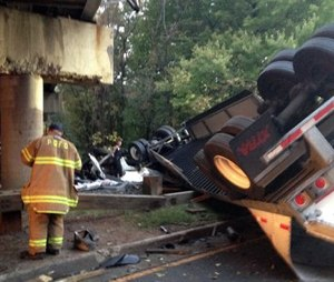 The wreckedtractor trailer lies under an overpass from which it fell Friday; the driver was killed and no one else was injured. (Assistant Fire Chief Alan C. Doubleday/Prince George's County, Md. Fire Department via AP)
