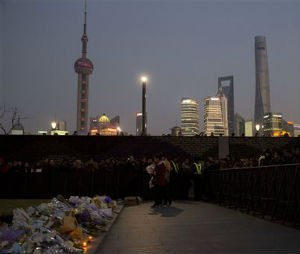 A woman prepares to lay flowers at the site of a deadly stampede in Shanghai, China, Thursday, Jan. 1, 2015. People unable to contact friends and relatives streamed into hospitals Thursday, anxious for information after a stampede during New Year's celebrations in Shanghai's historic waterfront area killed dozens of people in the worst disaster to hit one of China's showcase cities in recent years. (AP Photo/Ng Han Guan)