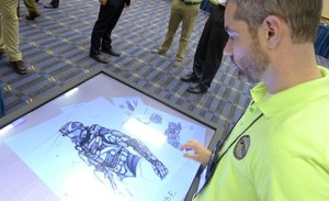 In this May 20, 2014 photo, Michael Fieldson , the civilian project manager for the Tactical Assault Light Operator Suit at McDill Air Force Base, looks at sketches of the body armor exoskeleton during the Special Operations Forces Industry Conference in Tampa, Fla.