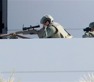 A Tucson Police sniper and a spotter watch a man in the parking lot of the Tucson Police Flowing Wells substation.