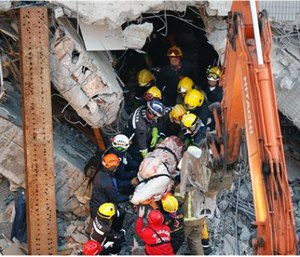 Emergency rescuers remove a body found in a collapsed building from an earthquake in Taiwan, Sunday. (AP Photo/Wally Santana)