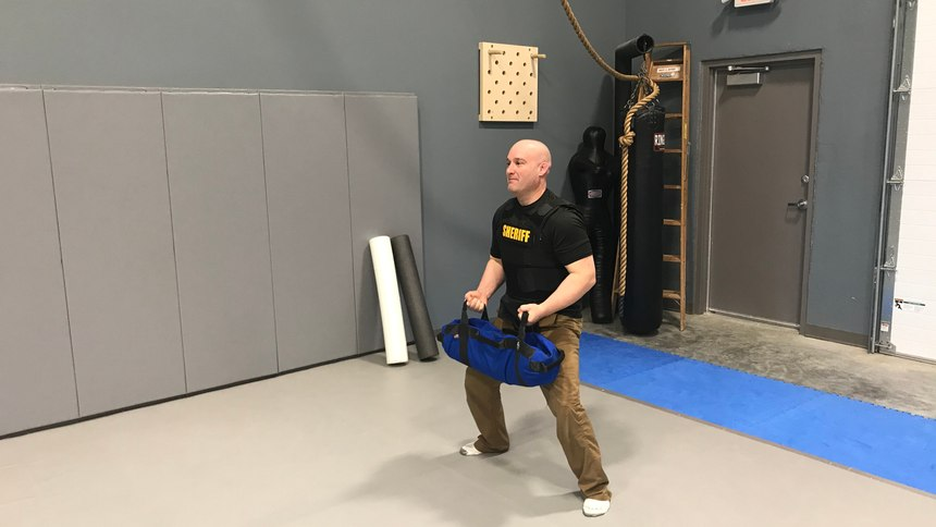 Because a sandbag's weight shifts inside the bag itself, you are forced to adjust and use stabilization muscles that you would not normally engage with free weights.