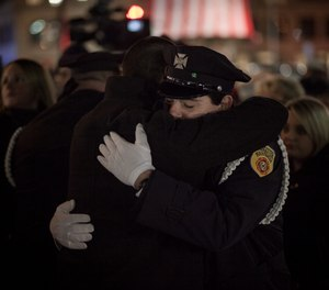 Jeremiah M. Lucey III embraces one of the Brotherton brothers after the memorial ceremony on Tuesday, Dec. 3, at the Franklin Street Fire Station. (Photo/Douglas Hook, masslive.com)