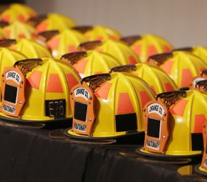 Firefigher helmets are lined up during graduation ceremonies for the recruit class of the Orange County Fire Rescue Department at Valencia College Performing Arts Center on Friday, December 14, 2018. (Photo/Stephen M. Dowell of the Orlando Sentinel)