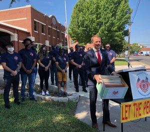 Pflugerville Professional Firefighters Association President Josh Stubblefield holds a box containing petitions that more than 4,000 people have signed to call for the formation of a new emergency services district that would fund EMS operations.