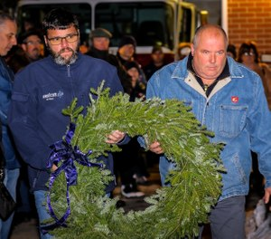 Two members of Firefighter Jon Davies' crew, Rescue 1 Group 4, carry a wreath to place next to the memorial at the Franklin Street fire station on Sunday, the eighth anniversary of Davies' death in the line of duty. (Photo/Dylan Azari)