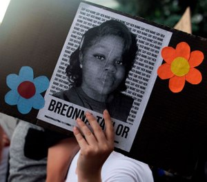 A demonstrator holds a sign with the image of Kentucky EMT and ER Technician Breonna Taylor at a protest in Denver, Colorado, June 3, 2020. Taylor was fatally shot by Louisville Metro Police Department officers during a drug raid at her home. (Photo/Jason Connolly, AFP via Getty Images/TNS)