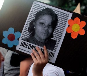 A demonstrator holds a sign with the image of Kentucky EMT and ER Technician Breonna Taylor at a protest in Denver, Colorado, June 3, 2020. Taylor was fatally shot by Louisville Metro Police Department officers during a drug raid at her home.