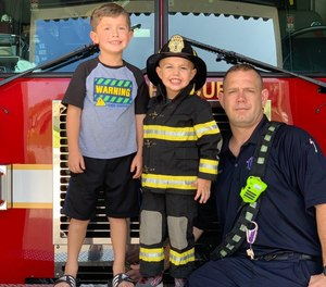 Firefighter Chris Shell with his sons Ari (left), 5, and Asher, 3. A video of the boys driving a toy fire truck, putting out a fire and performing CPR on a dummy has been viewed more than 2.3 million times on Facebook.