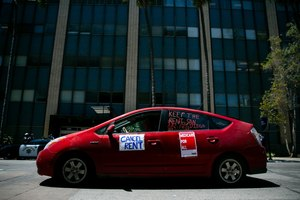 Protesters pass through downtown San Diego demonstrating from their cars as part of a