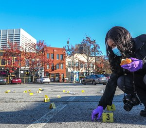 Atlanta Police Crime Technician K. Gallagher collects dozens of shell casings following a shooting outside a downtown Atlanta hookah lounge on Nov. 30, 2020.