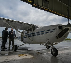 Eric Melancon, chief of staff for the Baltimore Police Department, left, and Ross McNutt, founder of the Persistent Surveillance Systems, look over a surveillance plane before it started flying over Baltimore.