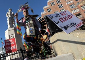 Andrew Thompson of the Choctaw Nation of Oklahoma brings his dance down the steps at the statue of Christopher Columbus at a rally for Indigenous Peoples' Day on Fri., Nov. 29, 2019. Image: Karl Merton Ferron/Baltimore Sun via TNS