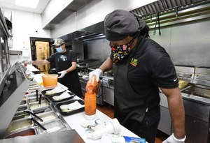 Ronald Showers (right) and Carlos Botello (left) in the kitchen of Billy's Sports Grill in Birmingham using masks and gloves. Image: al.com/Joe Songer via TNS