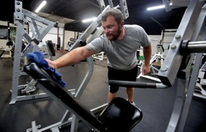 Kevin Nunns cleans gym equipment with hospital-grade disinfectant at the Lifting Lab in Shelby on Thursday. Nunns plans to open his gym despite N.C. Governor Roy Cooper's orders for gyms to remain closed until phase three. Image: Brittany Randolph/The Star via TNS