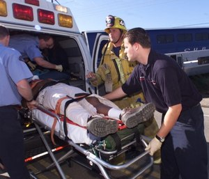 An American Medical Response paramedic, right, and a Ventura County firefighter help an injured man.
