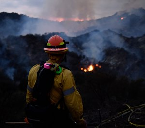 A firefighter watches flames from the Palisades Fire at Topanga State Park on May 15, 2021. An arson suspect has been arrested in the blaze that forced 1,000 people to evacuate and injured one firefighter.