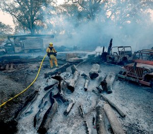 A firefighter mops up hot spots from the Kincade fire after it jumped Chalk Hill Road near Healdsburg, Calif. on Sunday morning, Oct. 27, 2019. (Luis Sinco/Los Angeles Times/TNS)