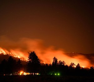 Trees burn on a hillside behind Honey Lake campground during the Dixie Fire on August 18, 2021 in Milford, California.