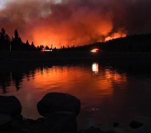 The Caldor fire is reflected off of Caples Lake near the Kirkwood ski resort Wednesday, September 1, 2021 in Lake Tahoe, California.