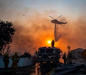 A helicopter drops water on burning mobile homes to try and keep the Sandalwood fire from spreading at Villa Calimesa mobile home park on Thursday, Oct. 10, 2019, in Calimesa, Calif. (Gina Ferazzi/Los Angeles Times/TNS)